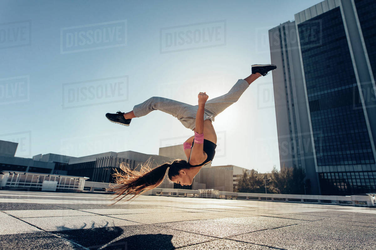 Young woman jumping high performing a frontflip outdoors in city. Female practicing tricking over urban city background. Royalty-free stock photo