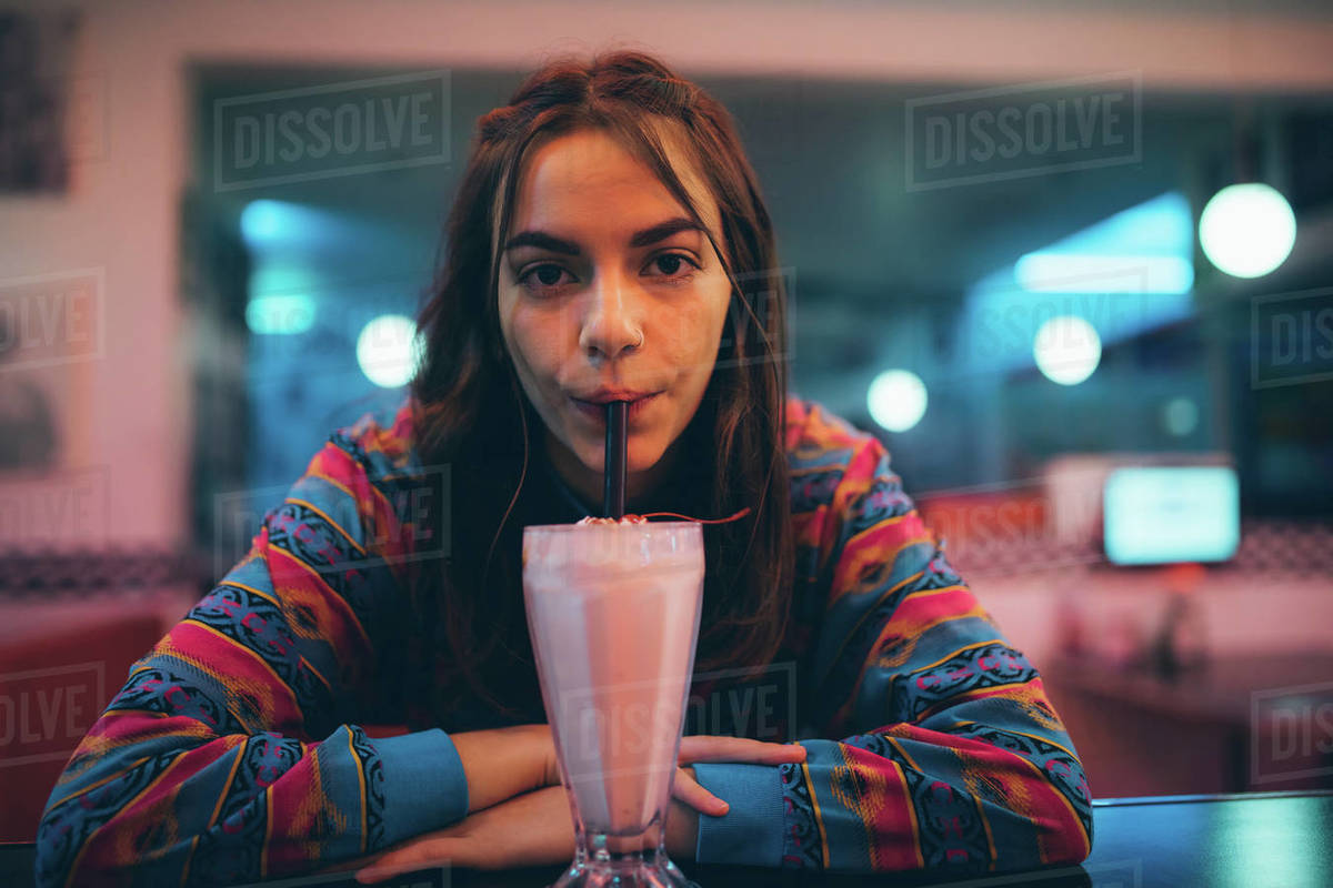 Woman drinking milkshake with straw at cafe. Female at cafe counter having drink. Royalty-free stock photo