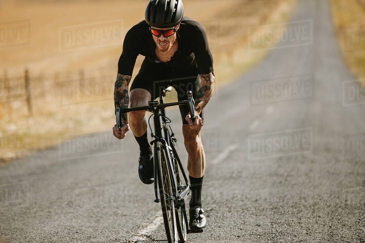 Fit man cycling outdoors on long road  Bicycle rider riding bike on asphalt  road in countryside  stock photo