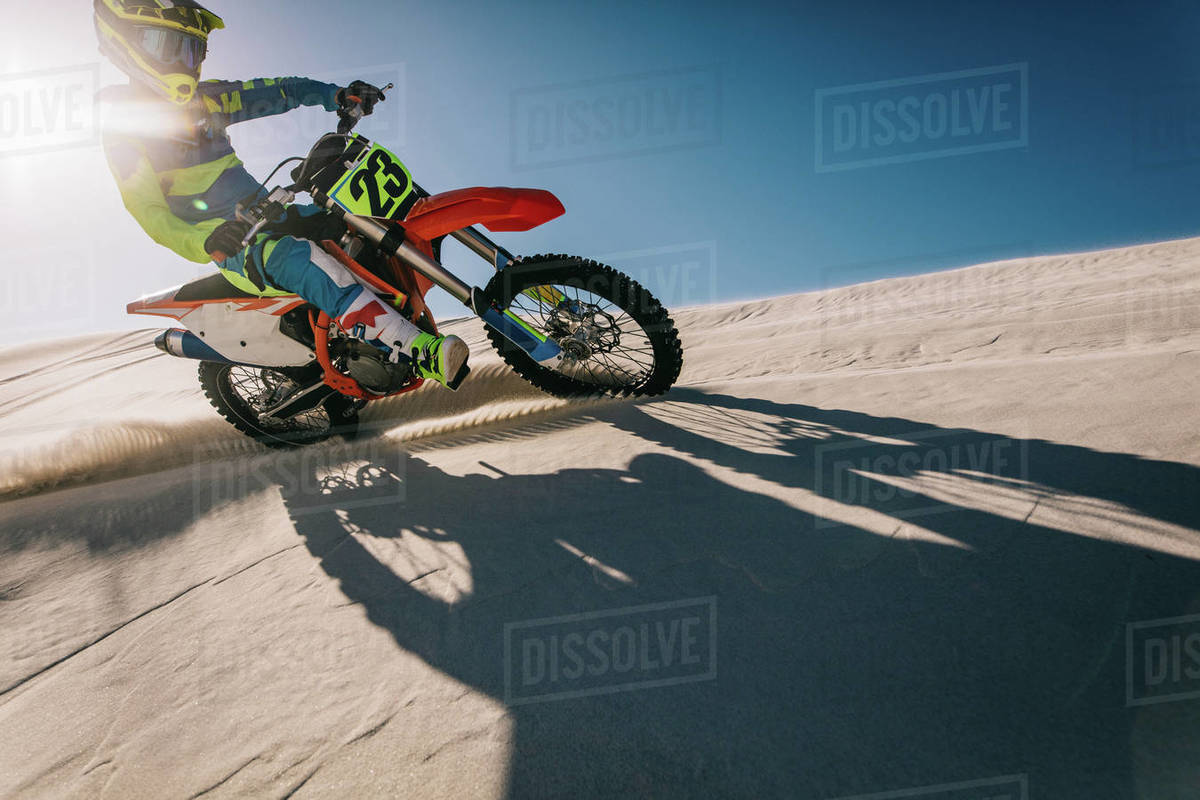 Motocross biker riding his racing bike on a sand dune with his shadow in front. Motorbike rider in racing gear riding up the sand dune leaving a trail of sand dust with sun in the background. Royalty-free stock photo