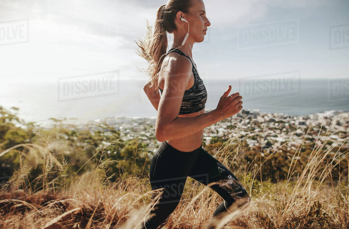Side view of fit young woman wearing earphones running through mountain trail. Female runner training over rough trail in hillside. Royalty-free stock photo