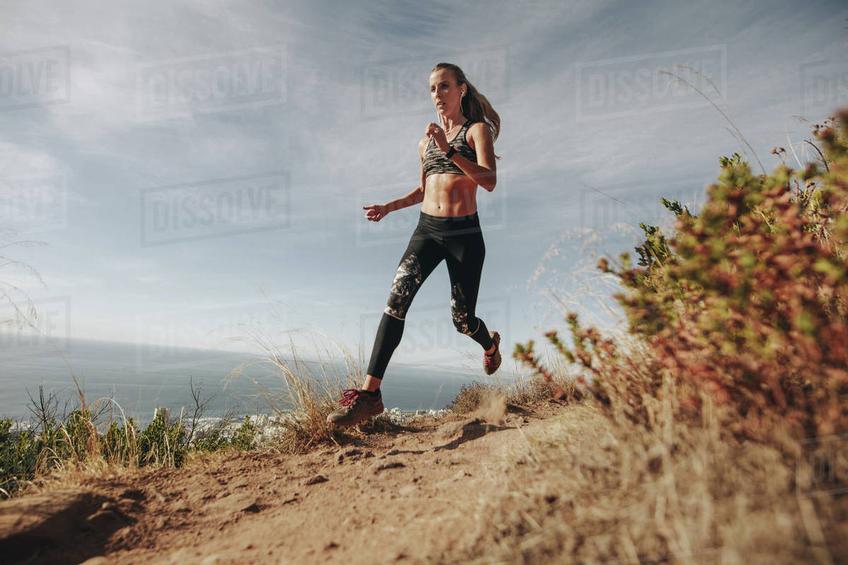 Fit sports woman sprinting over rocky trail on mountain. Woman running downhill on mountain path. Royalty-free stock photo