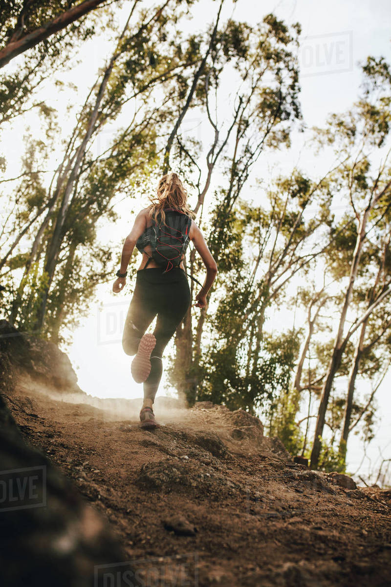 Rear view of woman running up hill. Trail running training. Fit athlete on cross country run over mountain. Royalty-free stock photo