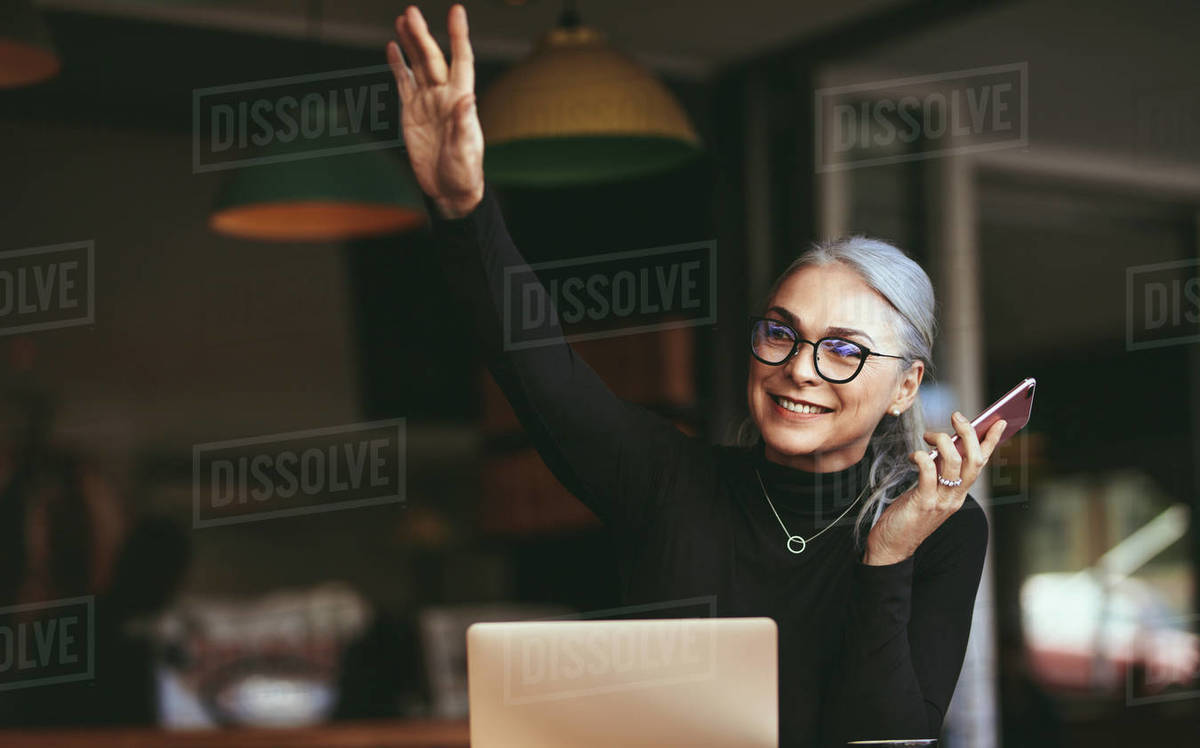 Portrait of happy senior woman sitting at cafe with laptop talking on mobile phone and waving at someone. Mature businesswoman at coffee shop. Royalty-free stock photo