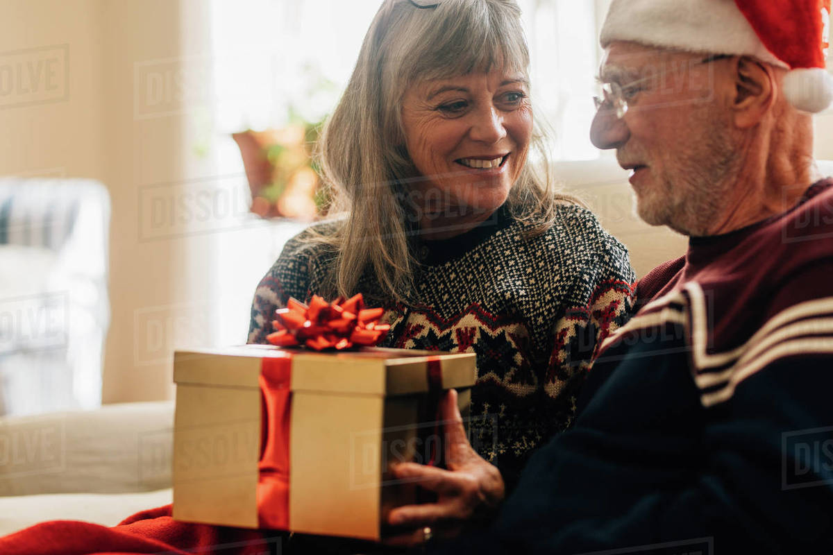 A Husband For Christmas.Elderly Woman Giving A Gift To Her Husband For Christmas Senior Couple Exchanging Gifts Celebrating Christmas At Home Stock Photo