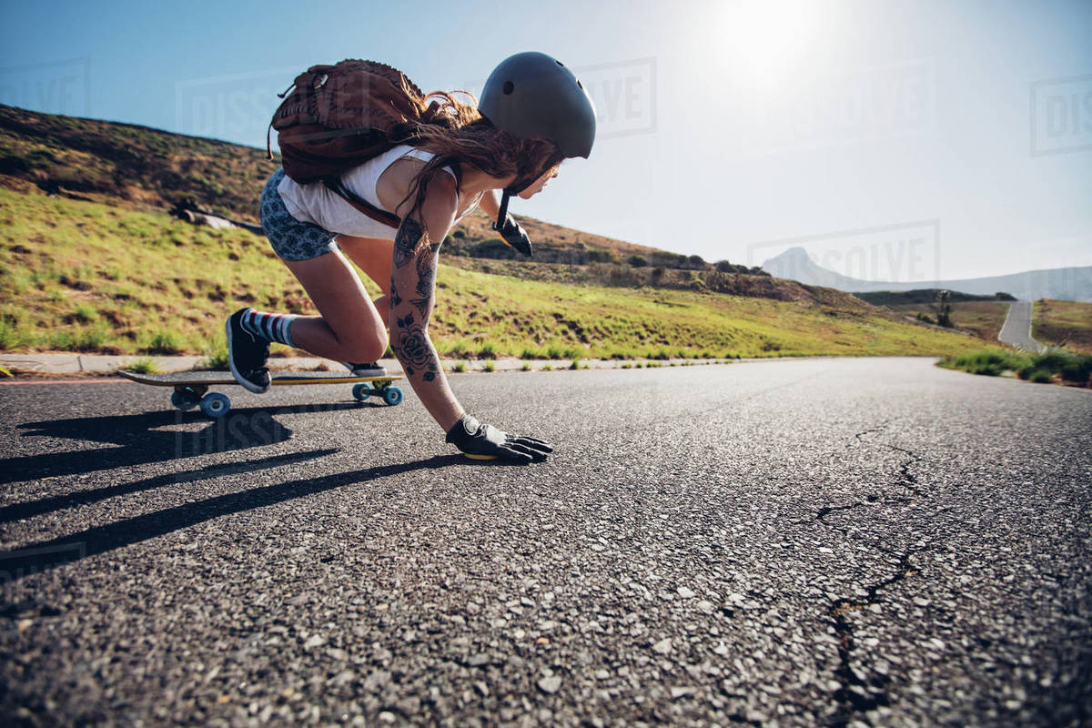 Young woman riding on her skateboard. Female skater practicing skating on country road. Royalty-free stock photo