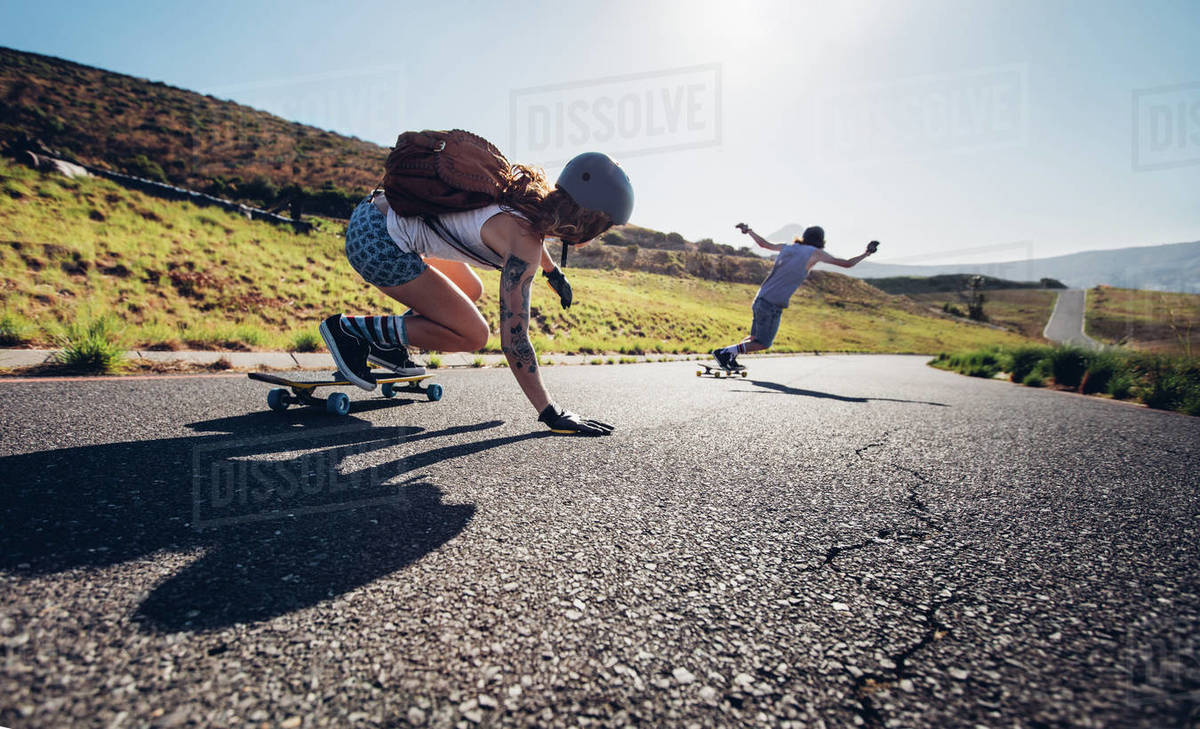 Young people skateboarding outdoors on the road. Young man and woman practicing skating on a rural road. Royalty-free stock photo