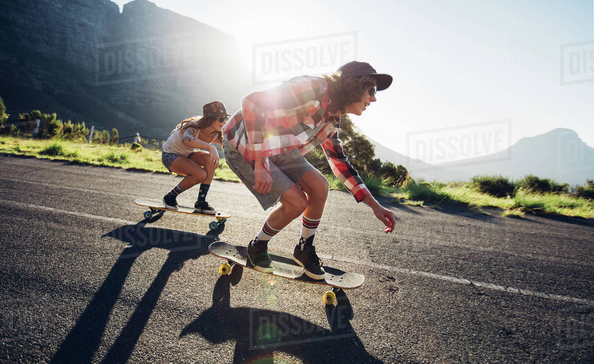 Side portrait of young people skateboarding together on road. Young man and woman longboarding down the road on a sunny day. Royalty-free stock photo