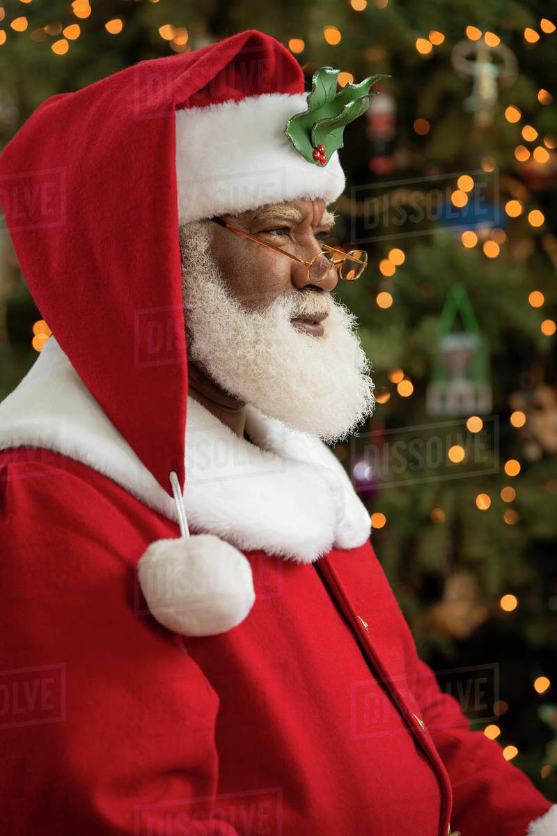 An African American man dressed as Santa Claus sitting in front of a Christmas tree turned profile, looking off camera. Royalty-free stock photo