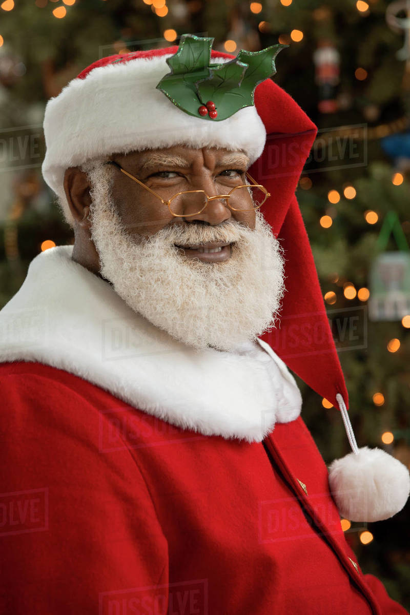An African American man dressed as Santa Claus sitting in front of a Christmas tree looking camera smiling.  Royalty-free stock photo