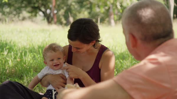 Happy people with infant doing picnic in city park. Family with man, woman and child eating, having fun outdoor. Leisure for dad, mom, baby boy. Slow motion Royalty-free stock video