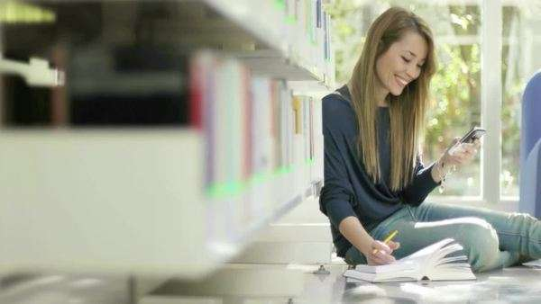Female college student sitting on floor in school library messaging on mobile phone. Dolly shot Royalty-free stock video