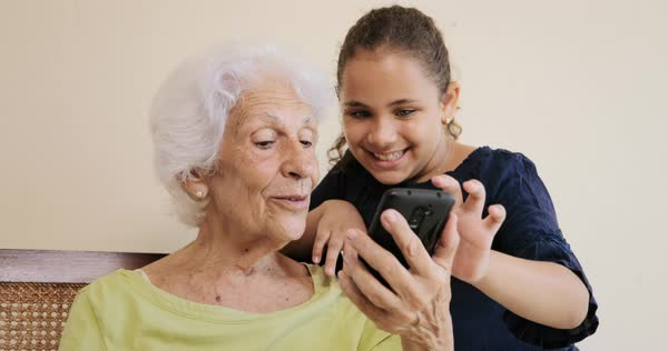 Grandma using mobile phone and kissing female grandchild Royalty-free stock video