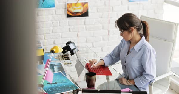 Woman working as photographer in studio. Woman with computer laptop for image review, editing. Artist doing art production work Royalty-free stock video