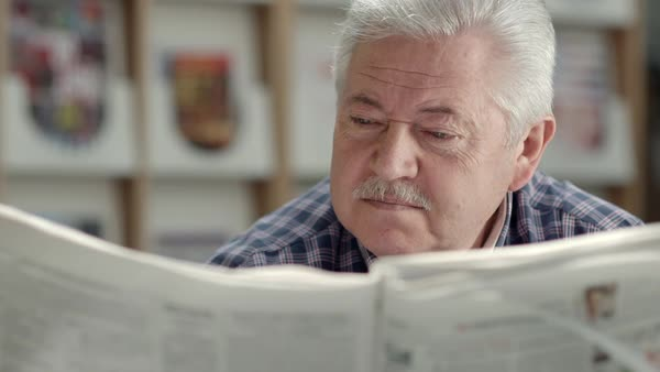 Seniors and active retirement, old man with mustache reading newspaper in city library Royalty-free stock video