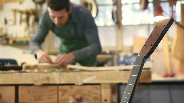 Man at work as craftsman in workshop with guitar and musical instrument, smoothing guitar body Royalty-free stock video