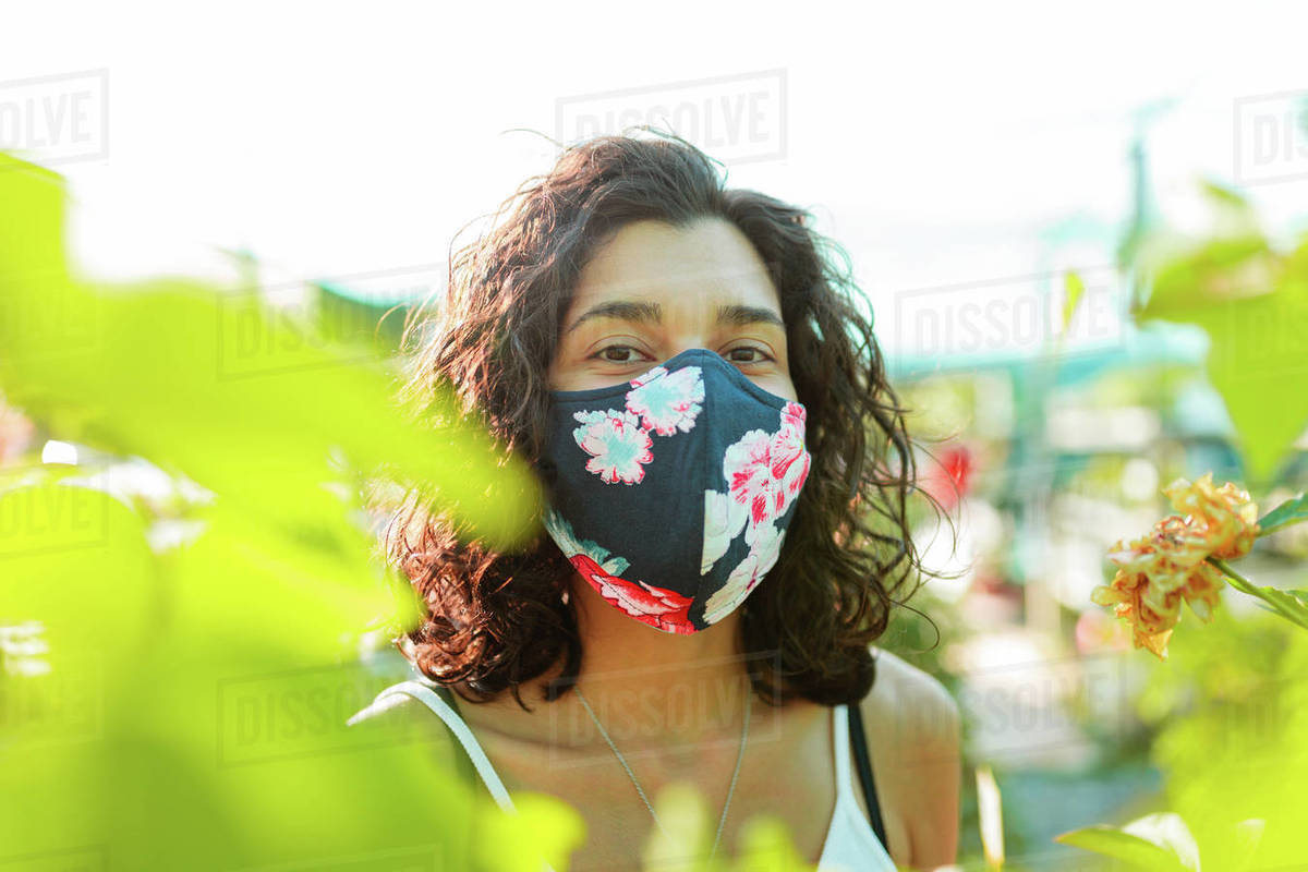 Woman with face mask gardening in greenhouse. People outdoor activities enjoying nature during pandemic coronavirus crises. Female with diy mask trought plants and flowers Royalty-free stock photo