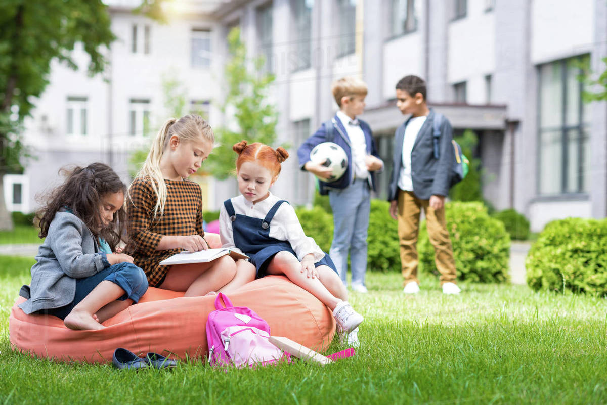 Remarkable Adorable Multiethnic Schoolgirls Sitting On Bean Bag Chair And Reading Book While Schoolboys Standing With Soccer Ball On Schoolyard Stock Photo Ocoug Best Dining Table And Chair Ideas Images Ocougorg