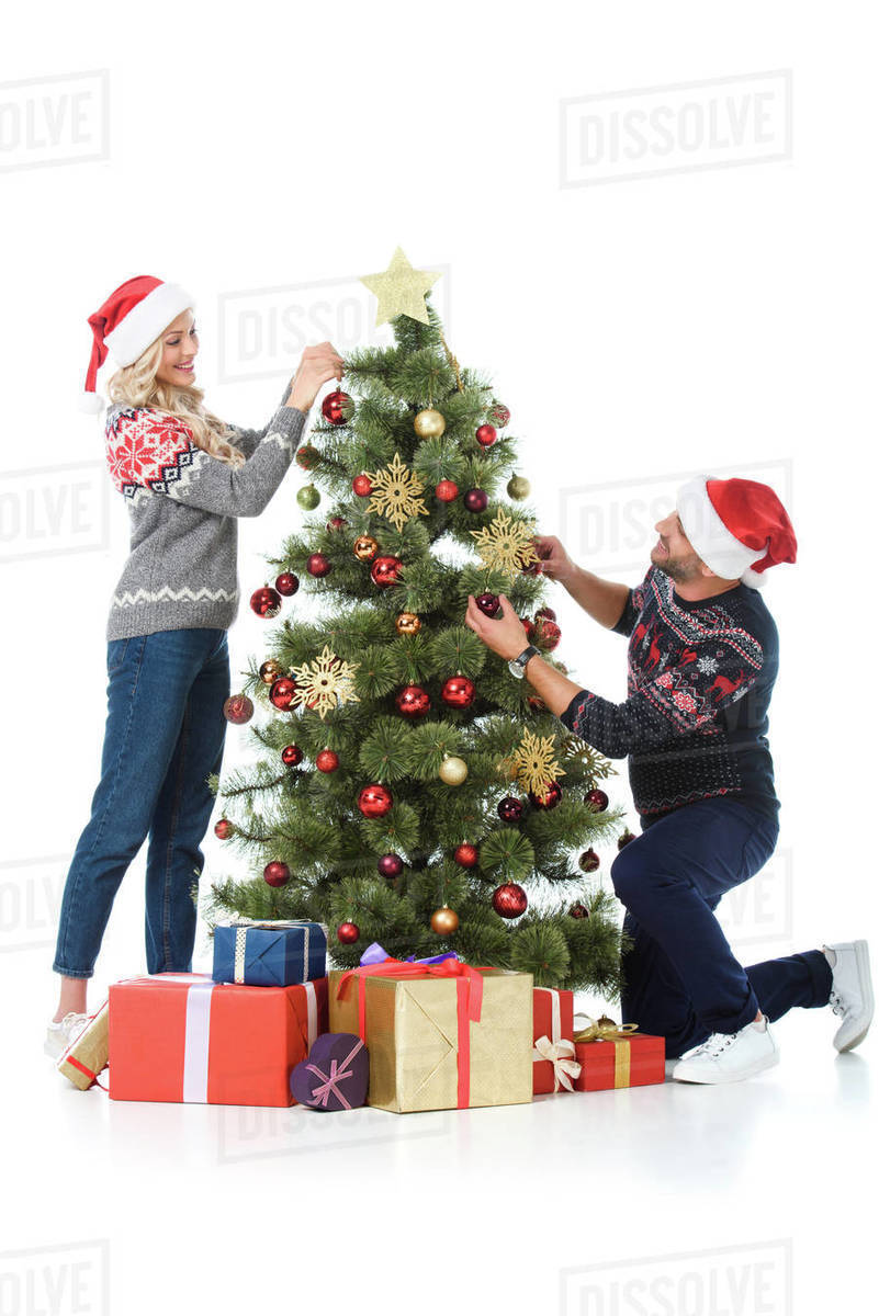 Christmas Tree With Presents.Happy Couple In Santa Hats Decorating Christmas Tree With Presents Isolated On White Stock Photo