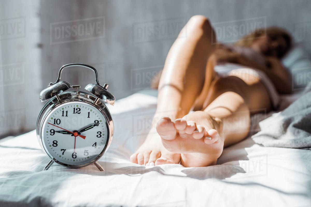 Close-up view of female feet and alarm clock in bedroom D2115_130_764