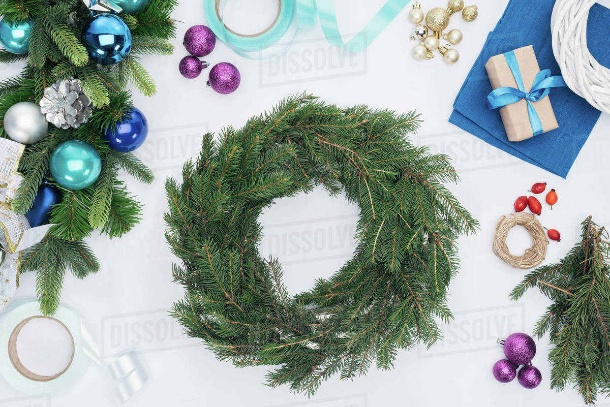 Top view of handmade Christmas wreath decorations and ribbons isolated on white
