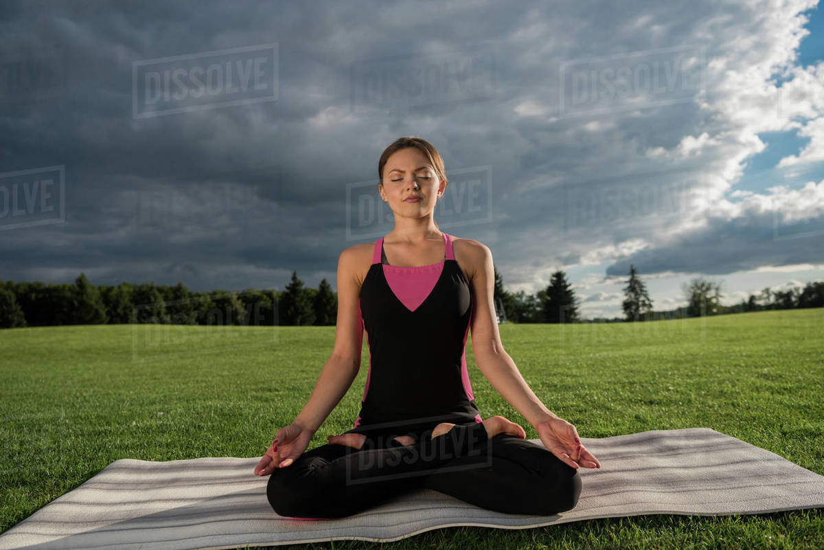 Woman with eyes closed practicing lotus pose while meditating alone in park  stock photo
