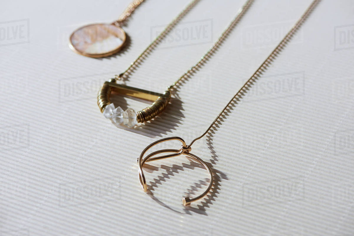 460dcb0959b20 Close up of beautiful luxury necklaces and round locket with marble on  striped white surface with sunlight stock photo