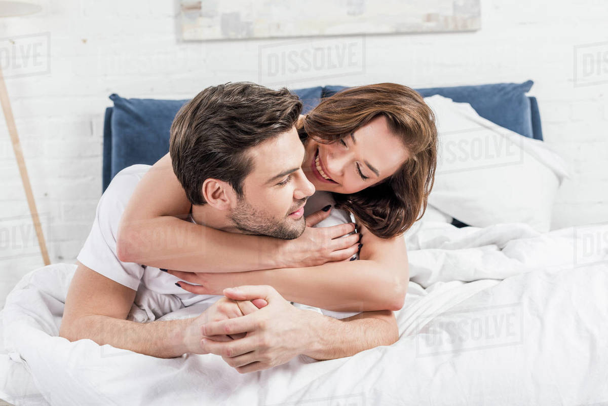 Beautiful Happy Couple Hugging In Bed At Home Stock Photo Dissolve
