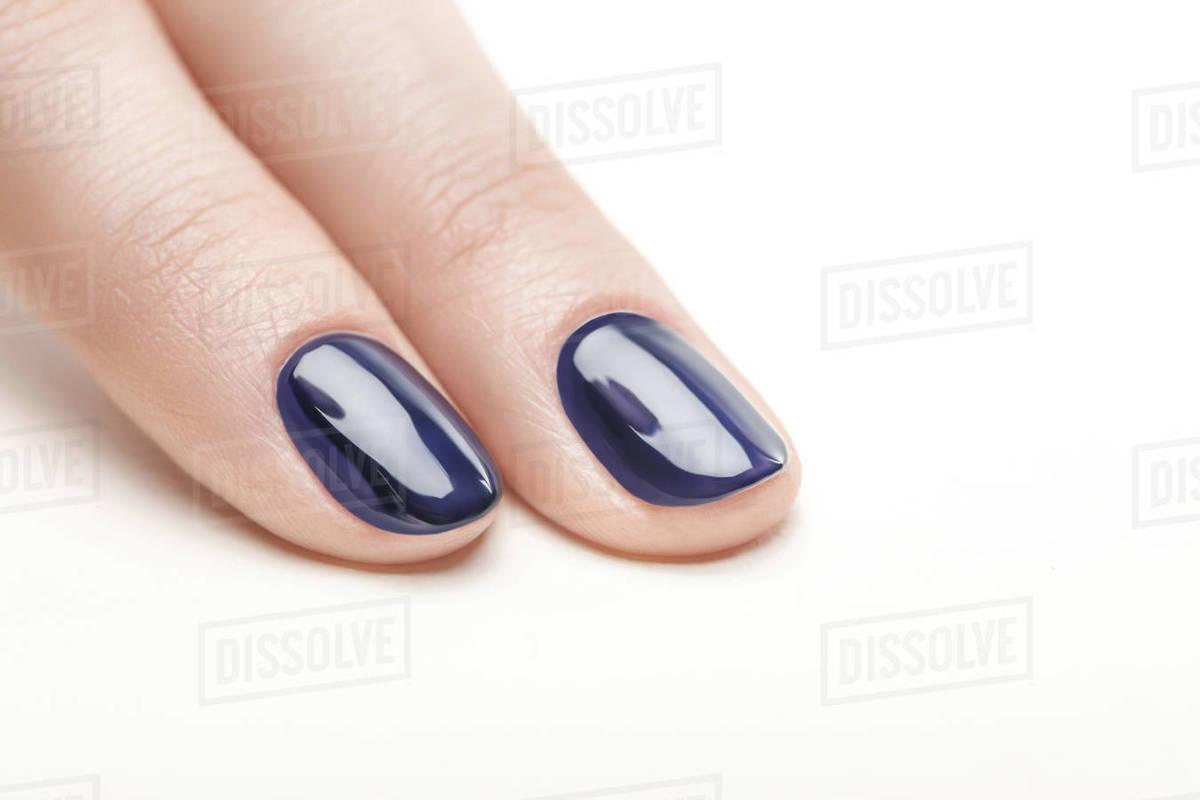 Fingernails with shiny navy blue nail polish on white background ...