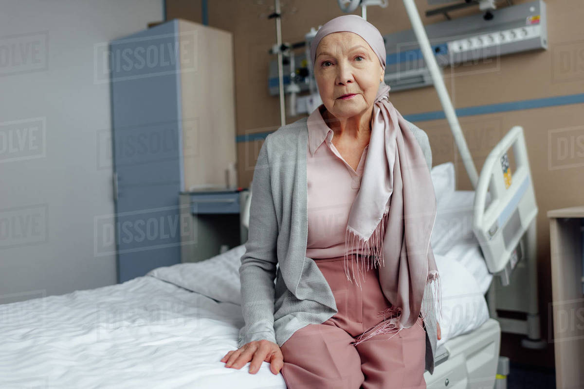 Sad senior woman with cancer sitting on bed in hospital and looking at  camera stock photo