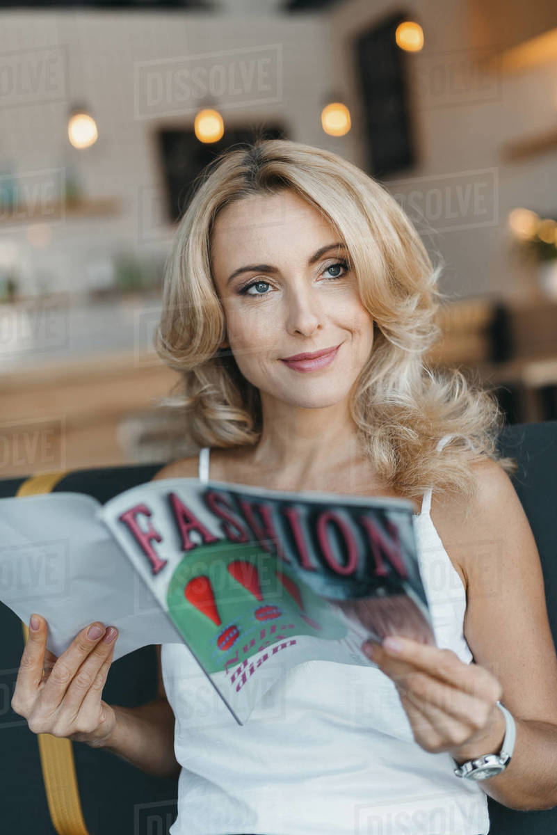 attractive happy mature woman reading fashion magazine and looking away in  cafe stock photo