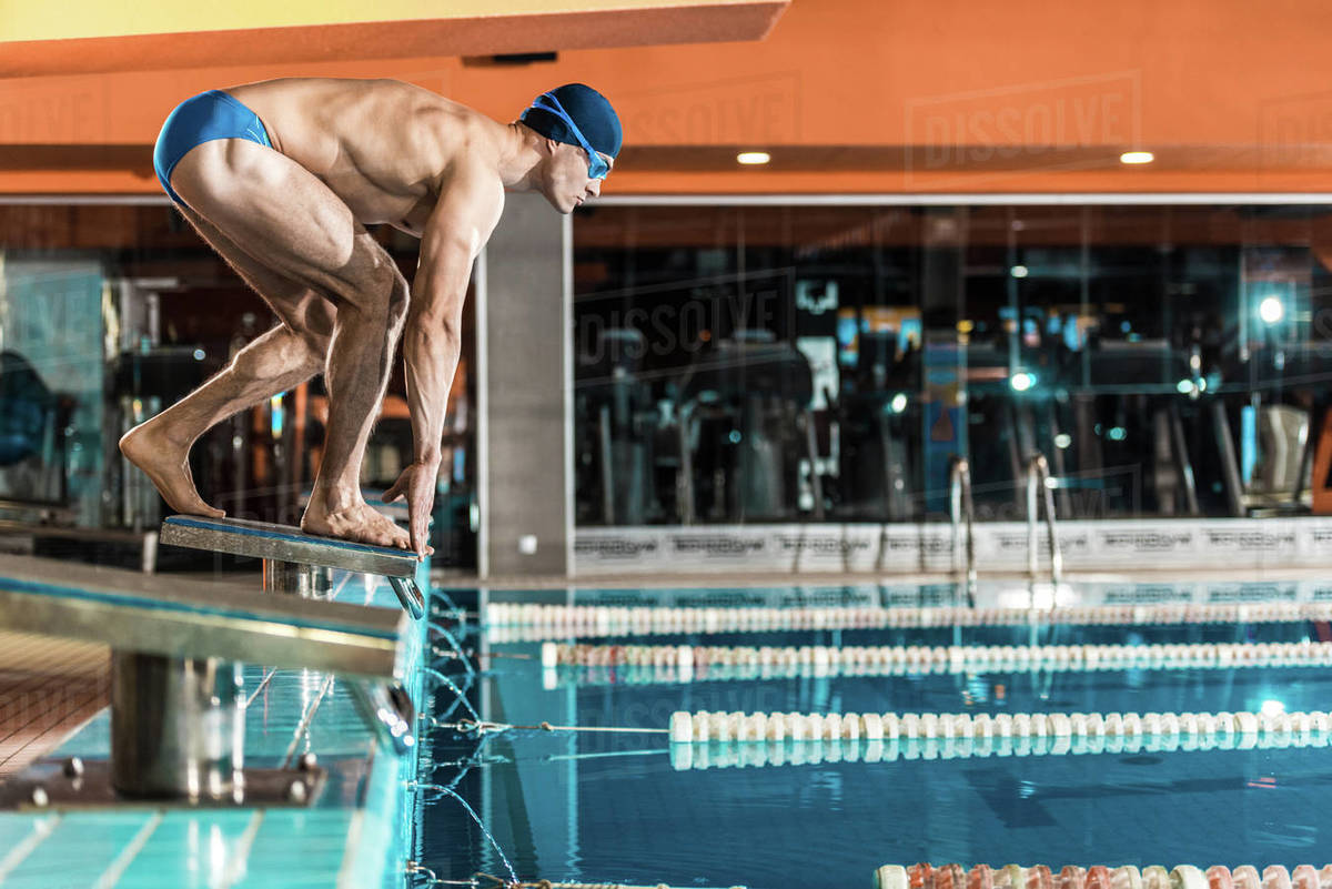 Swimmer standing on diving board ready to jump into competition  D2115_228_474