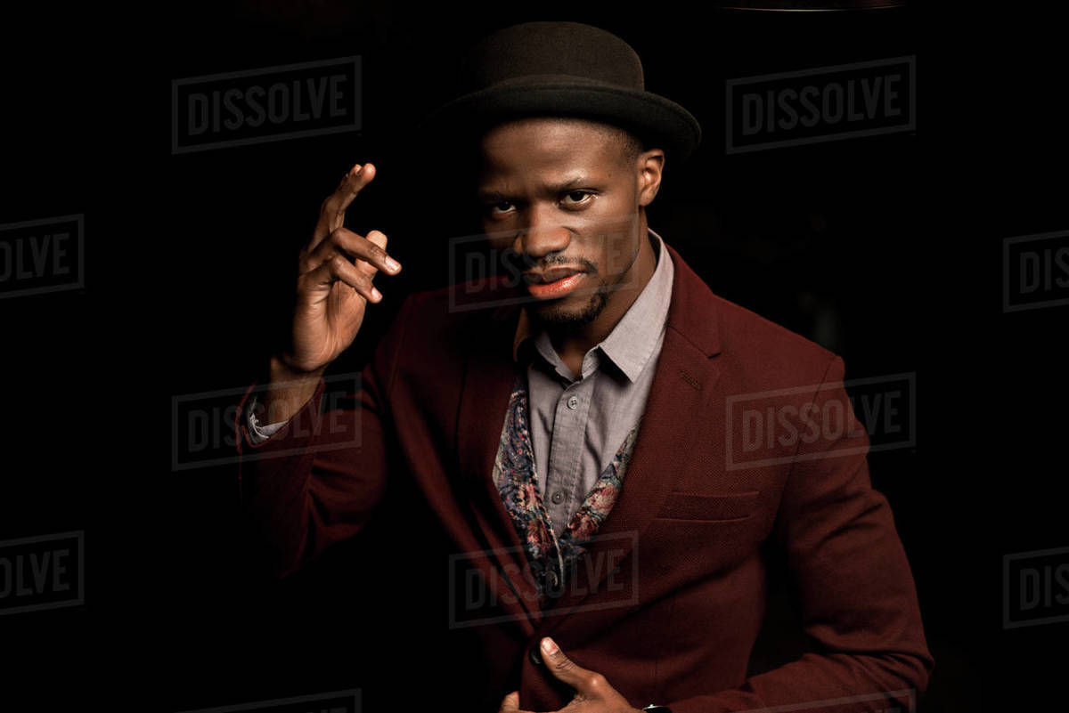 57a8166a Handsome fashionable African American man in hat gesturing isolated on black