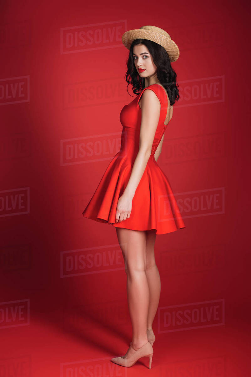 girl in red dress and straw hat posing