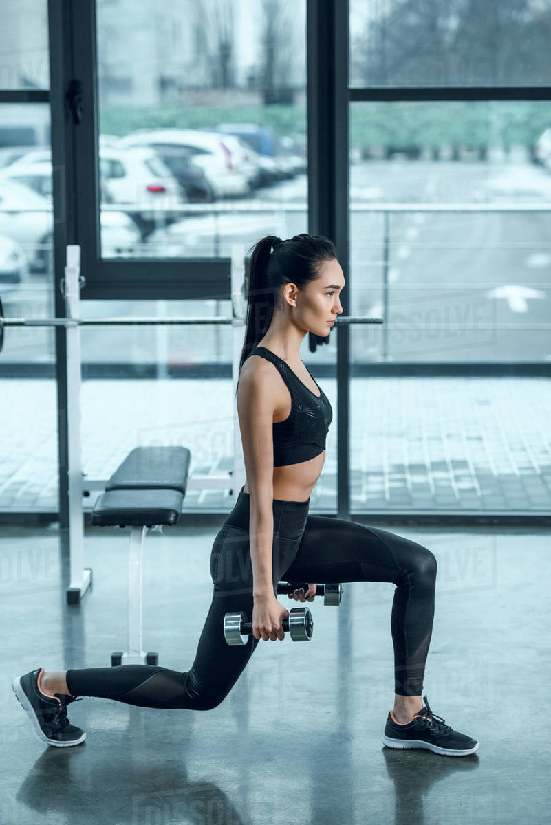 side view of young fit woman doing single leg squats with dumbbells at gym  stock photo