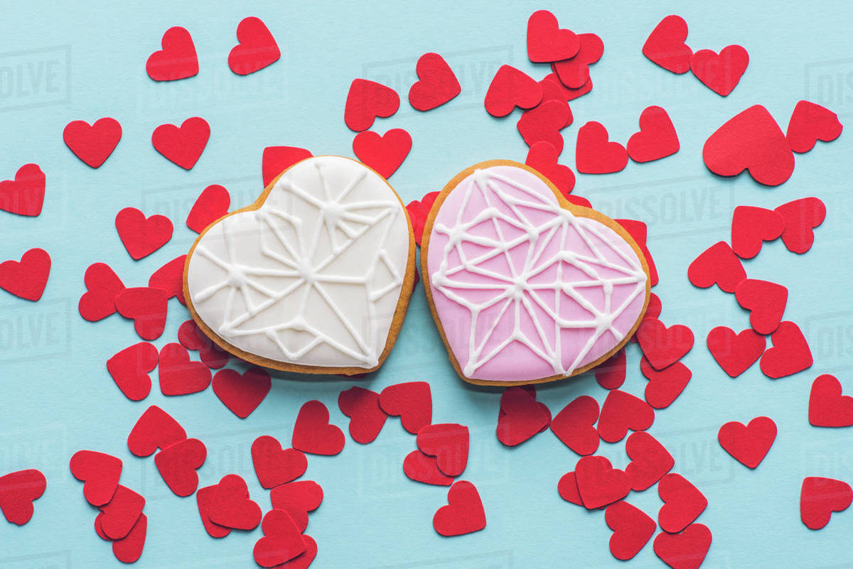 Top view of heart shaped cookies and red decorative confetti isolated on  blue stock photo
