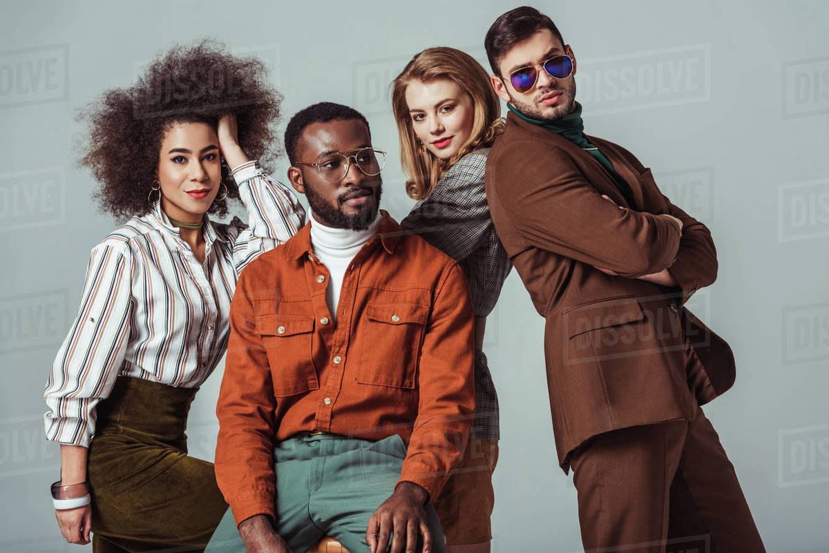 Multicultural retro styled friends posing isolated on grey Royalty-free stock photo