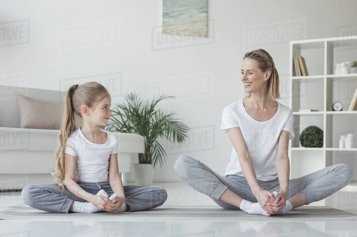 Mother and daughter practicing yoga in butterfly pose at home Royalty-free stock photo