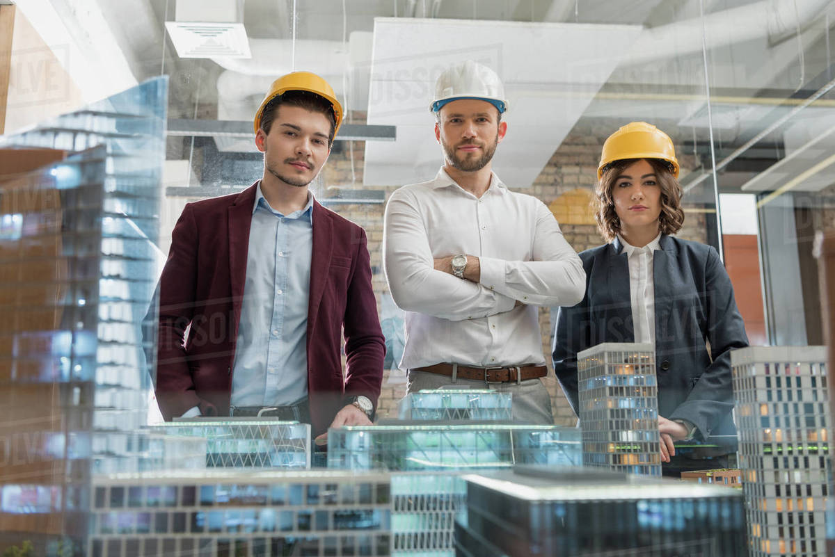 Team of architects in hard hats in front of miniature town model Royalty-free stock photo
