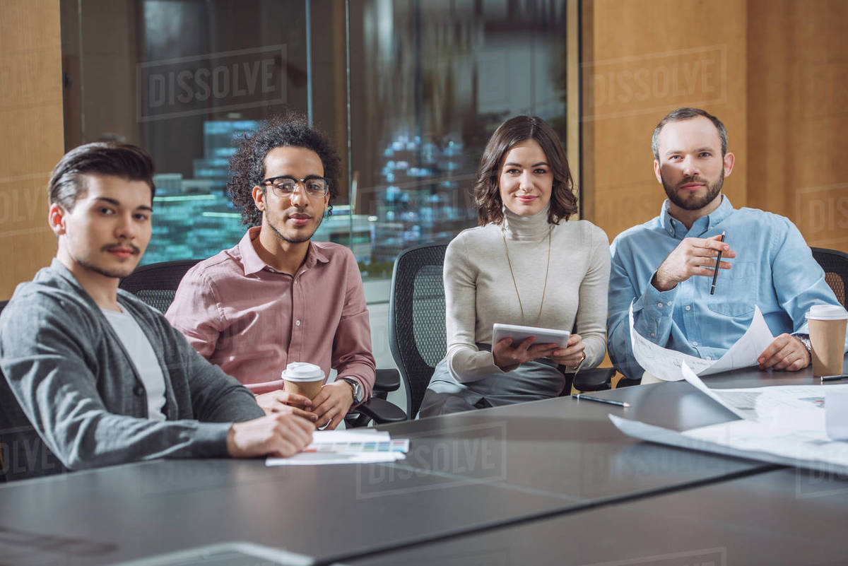 Group of businesspeople sitting in conference room together and looking at camera Royalty-free stock photo