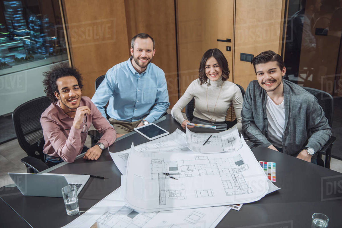 Group of successful architects sitting at conference hall at office and looking at camera Royalty-free stock photo