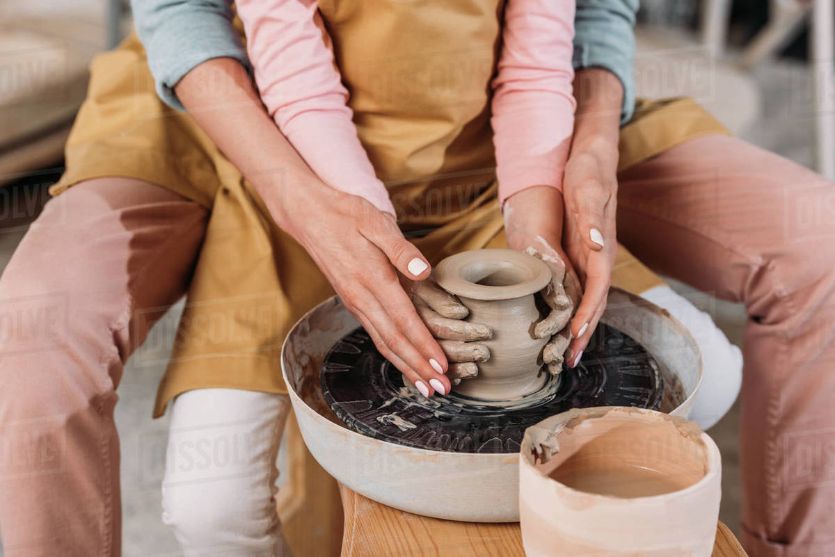Cropped View Of Teacher And Kid Making Ceramic Pot Together On Pottery Wheel Stock Photo Dissolve