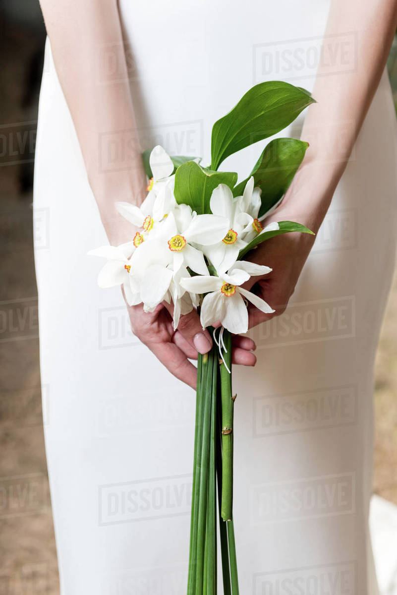Cropped view of bride holding wedding bouquet with white daffodils Royalty-free stock photo