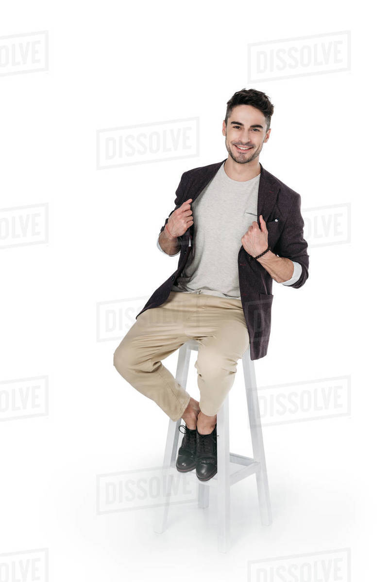casual african caucasian man posing while sitting on chair isolated on white Royalty-free stock photo
