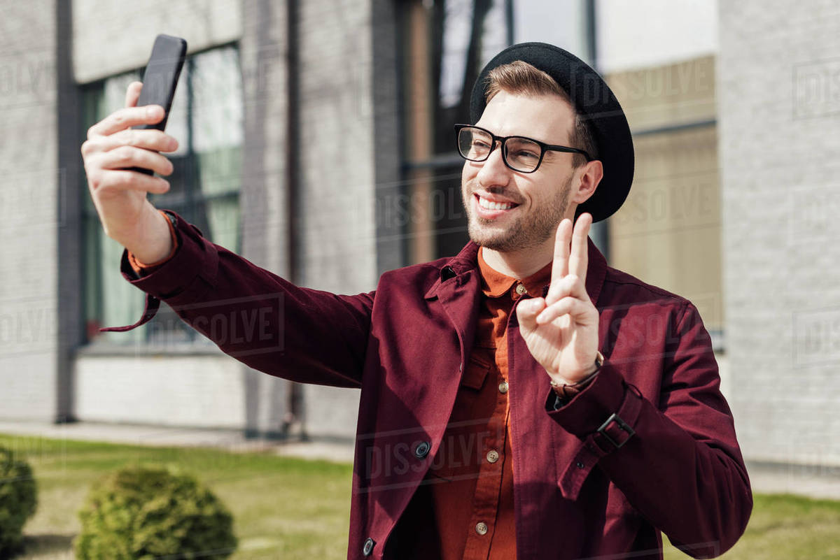 Handsome cheerful man showing peace symbol and taking selfie on smartphone Royalty-free stock photo