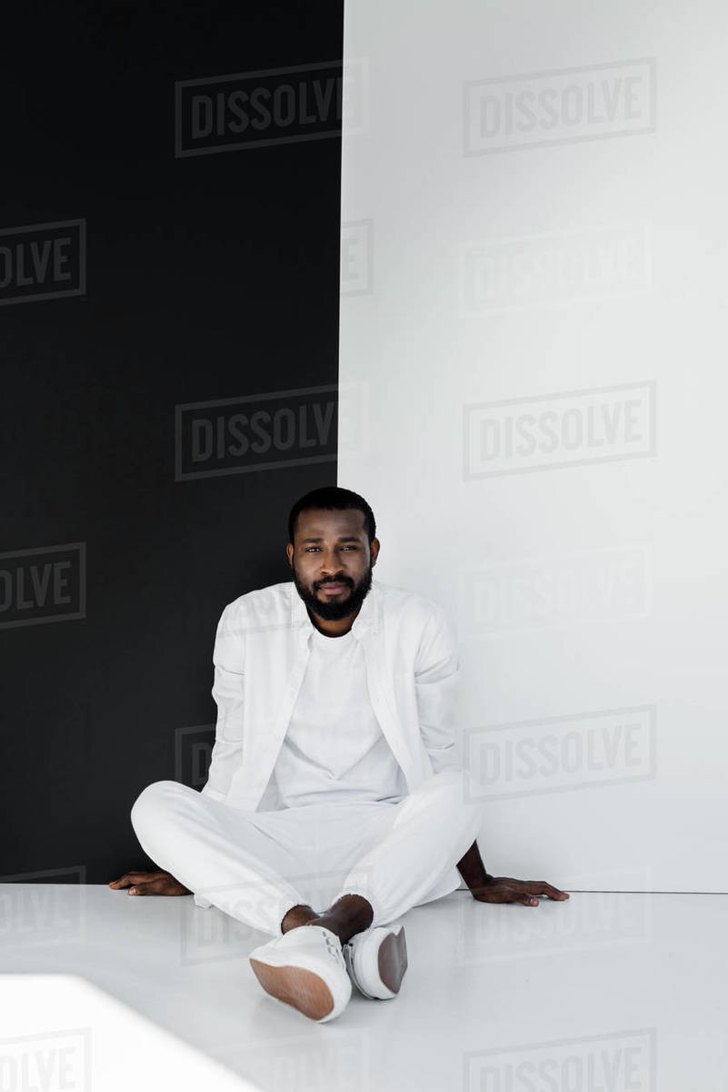 600e670d Handsome stylish african american man sitting on floor near black and white  wall