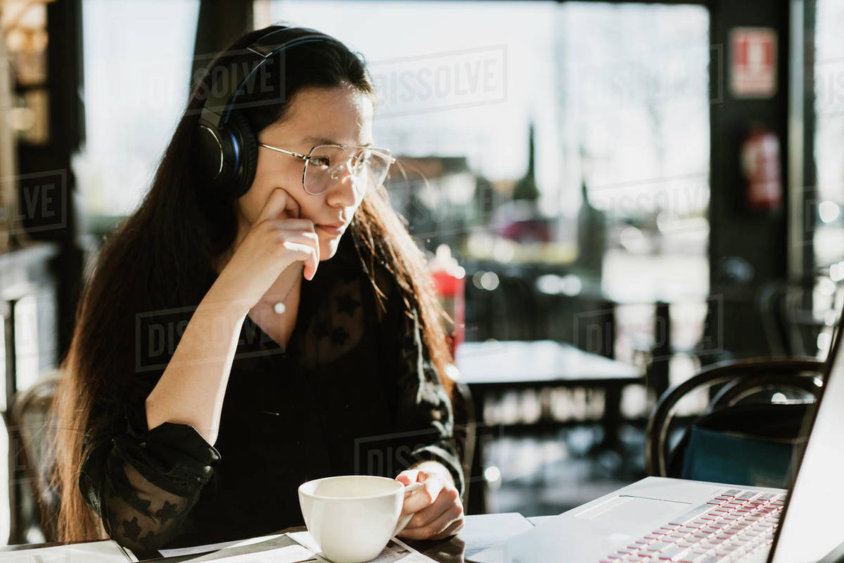 Asian woman working while drinking coffee in coffee shop Royalty-free stock photo