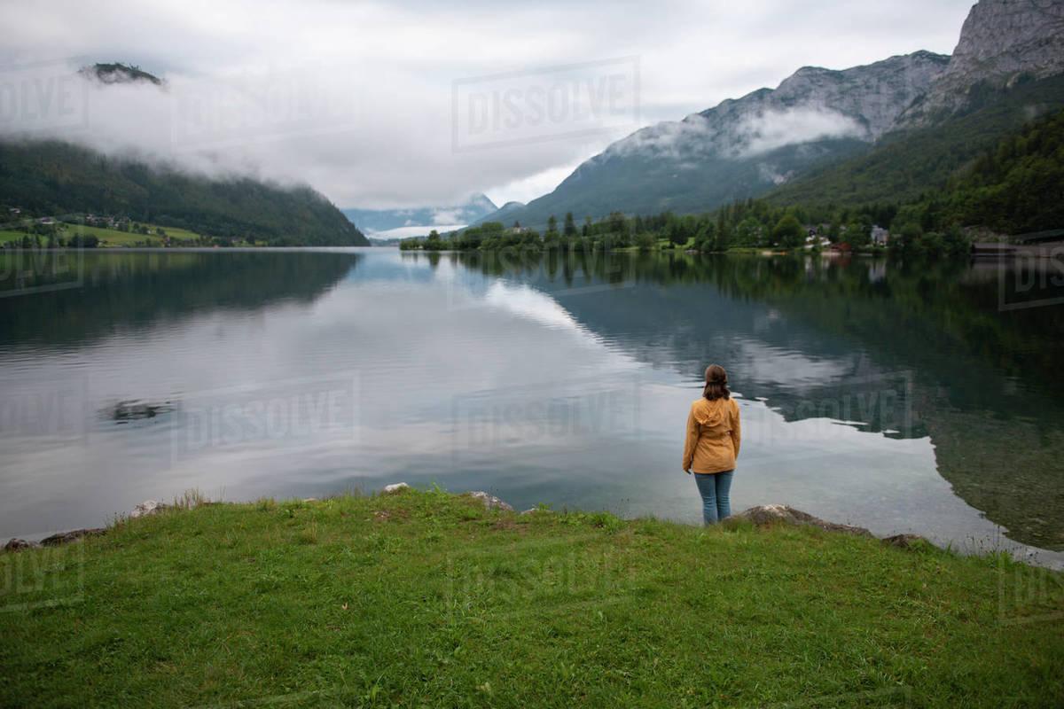 Woman standing at lake shore and looking at water Royalty-free stock photo