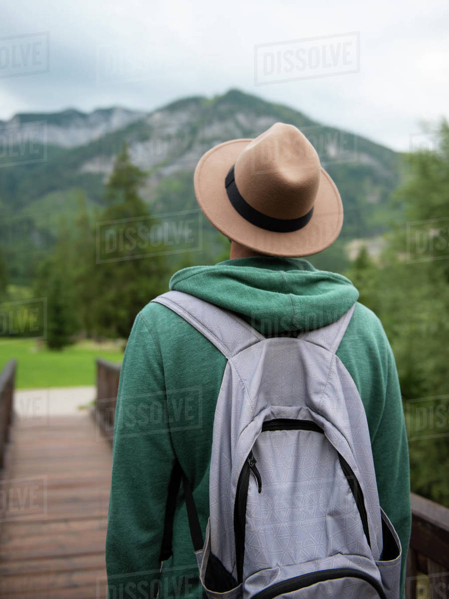 Back view of man in brown hat walking along wooden bridge in mountains Royalty-free stock photo