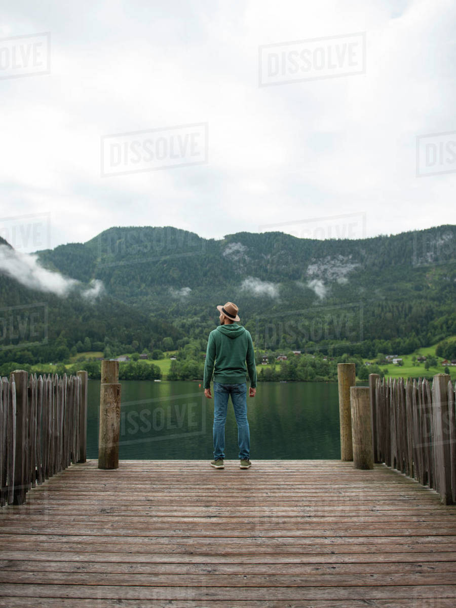 Back view of man standing on the edge of wooden pier and enjoying the lake view Royalty-free stock photo